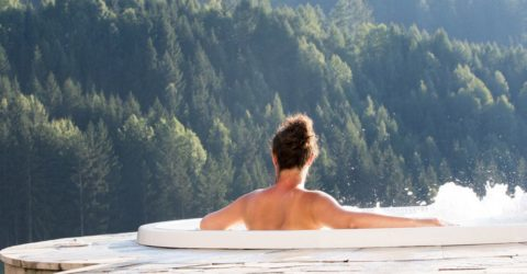 Topless woman enjoying view of forested mountain from hot tub