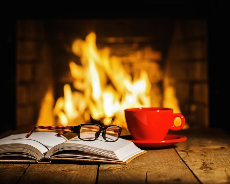 Table holding book, reading glasses, and mug in front of burning fireplace