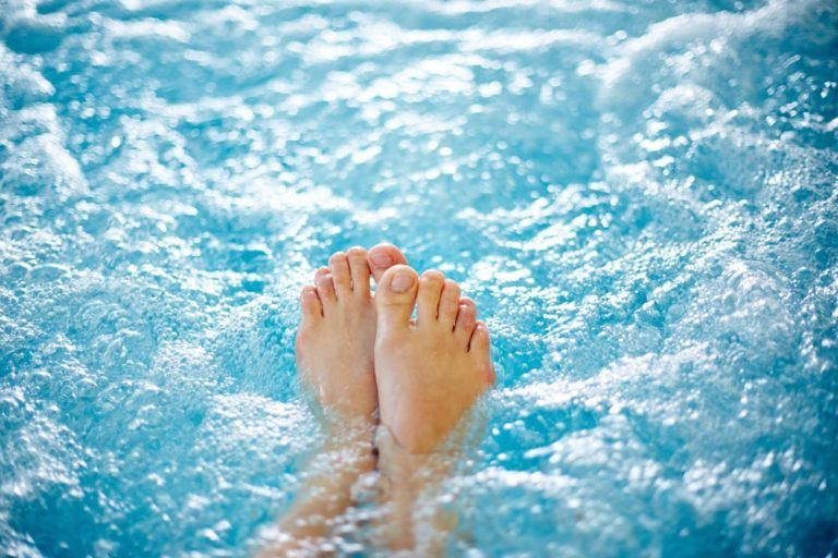Pair of feet sticking out of bubbling water.