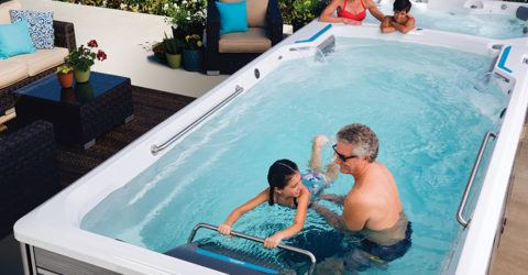 family of four swimming and lounging in an endless pool swim spa