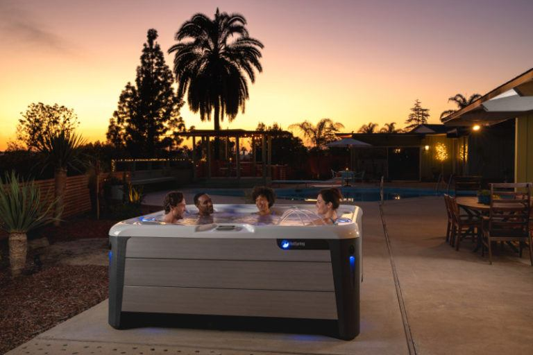 four people sitting in hot tub in a backyard as the sun goes down