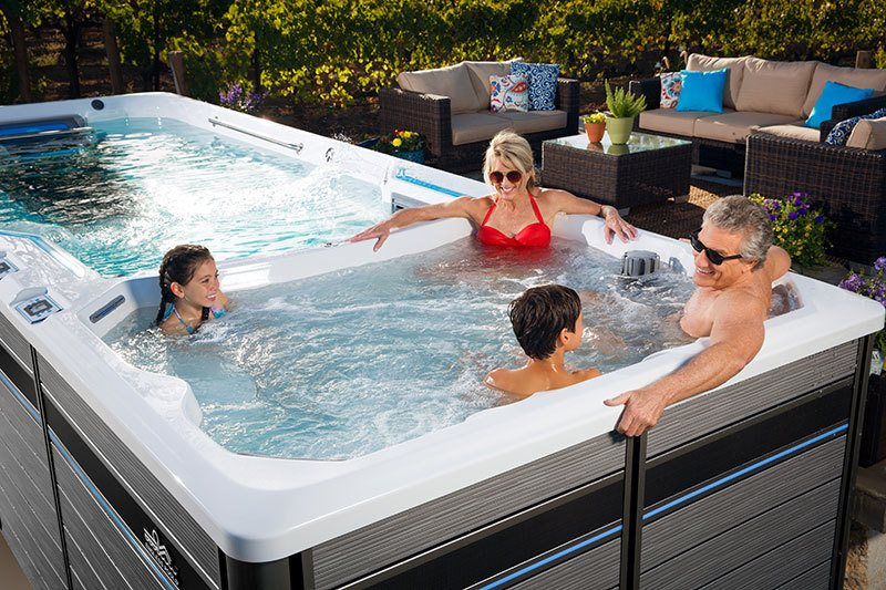 father, mother, and two children in the spa part of a endless pool swim spa
