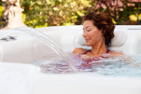 woman relaxing with eyes closed in backyard hot tub