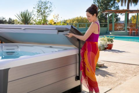 woman in a sarong lifting hot tub cover from spa