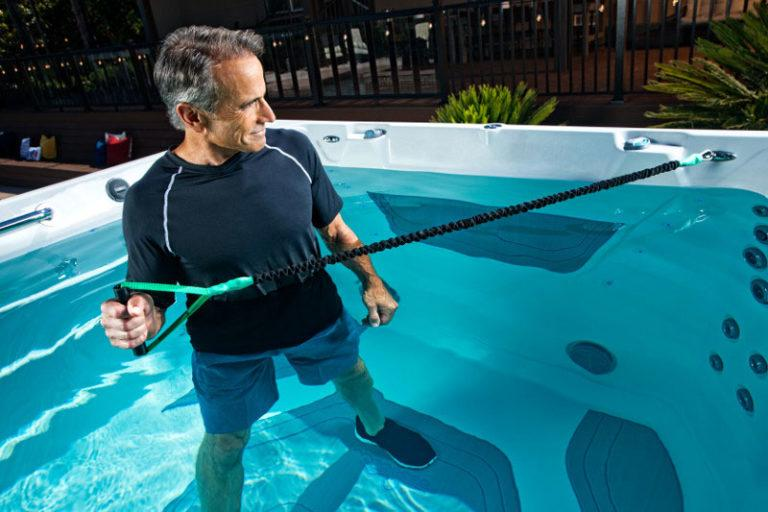 man working out with resistance bands in swim spa