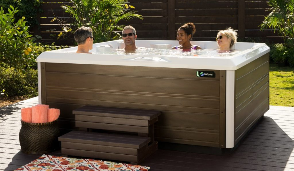 four people in a full size hot tub in backyard