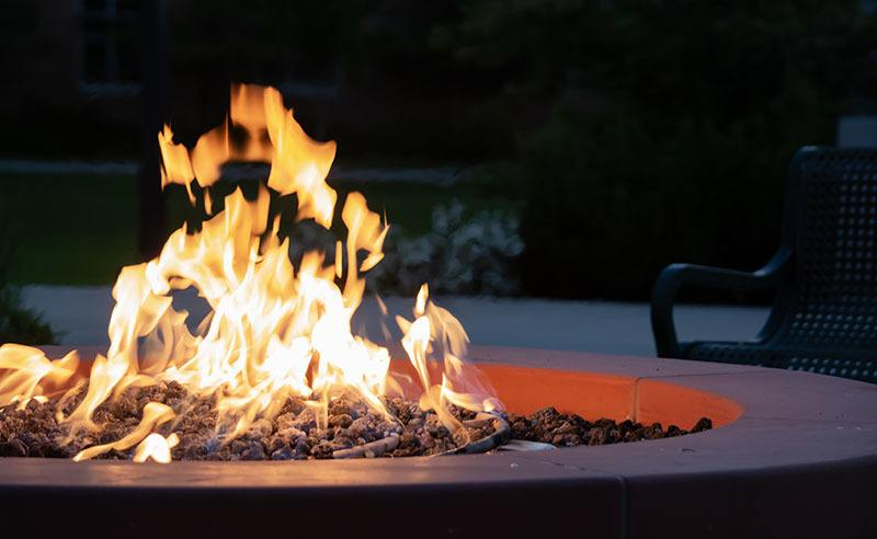 Close-up of a lit fire pit at night in a backyard