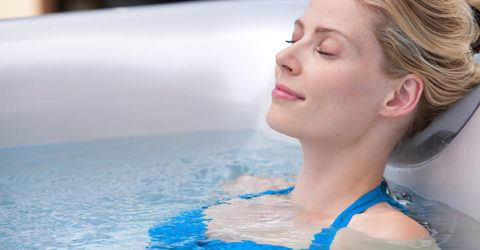 young woman relaxing in a hot tub looking very happy