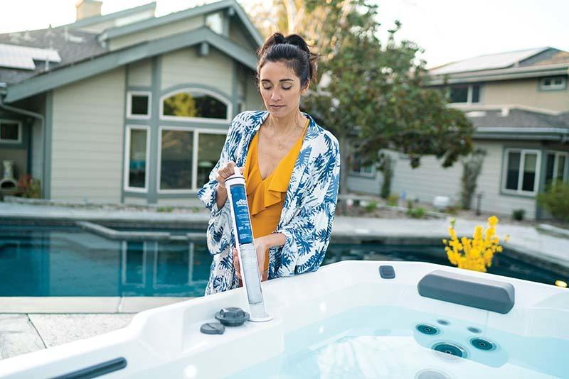 women using hot tub maintenance products to keep her spa clean