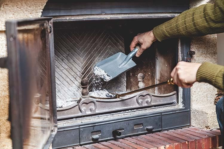 person cleaning a fireplace in springtime