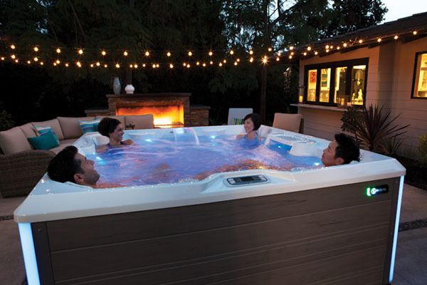 friends relaxing in a hot tub in a backyard on a summer evening