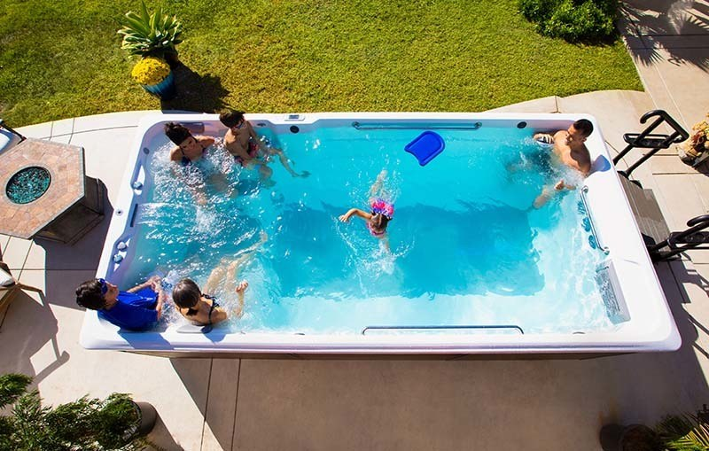 large family enjoying their endless pools swim spa in their backyard during the summer