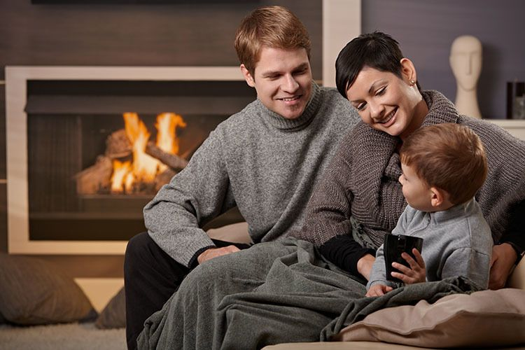 happy family sitting in front of their fire place smiling