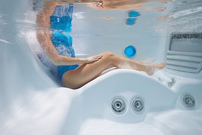Underwater view of Lounge Seat with woman enjoying massage jets