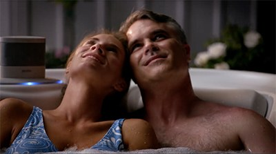 A couple enjoying a romantic soak in their HotSpring spa while listening to music on their wireless bluetooth speaker system