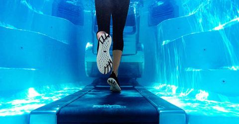 women running underwater on an aquatic treadmill in an Endless Pool Swim Spa