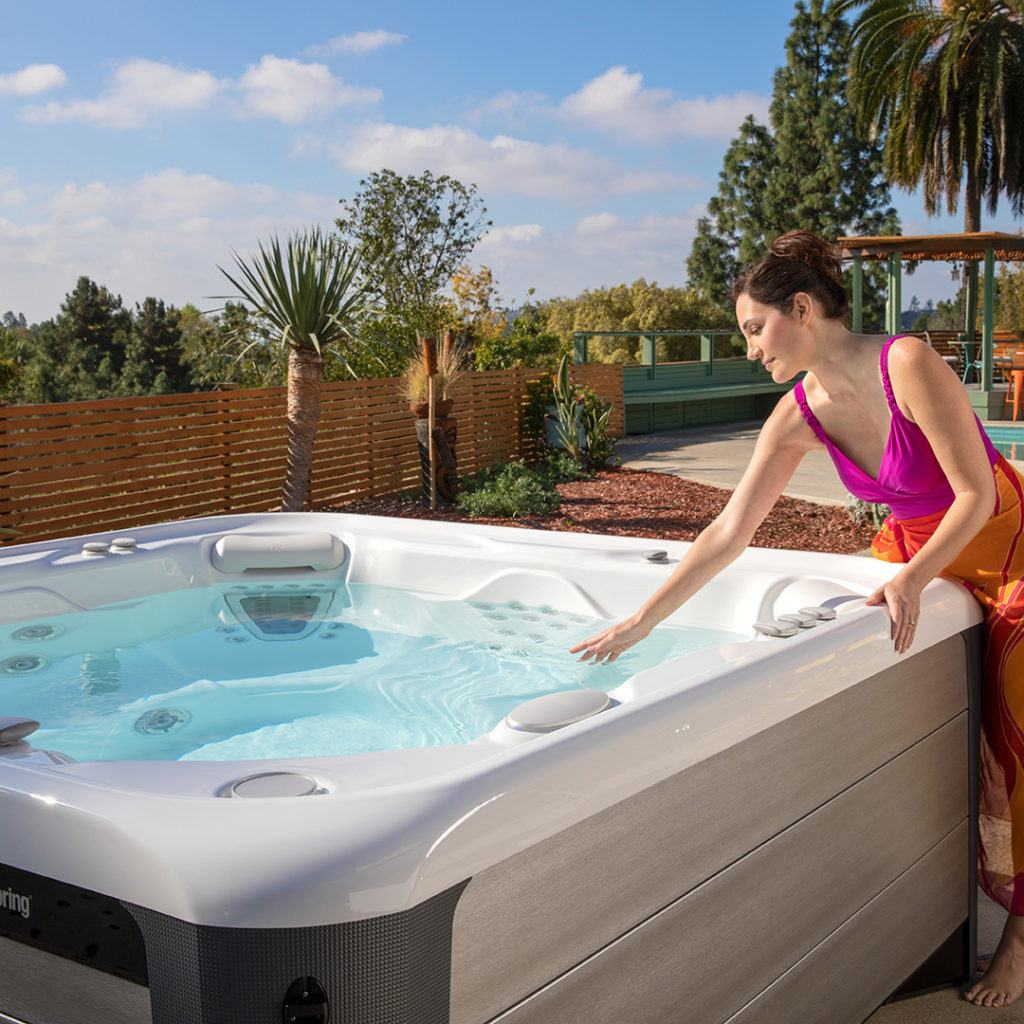 women in backyard looking into her hotsprings spa at brilliantly clean and clear hot tub water