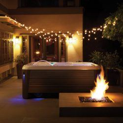 Spa on patio at night with string lights overhead and a lit fire pit in the foreground