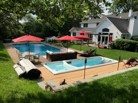 Lush green backyard with lawn, bushes and trees, and a full swim spa with deck and pool next to a white home.